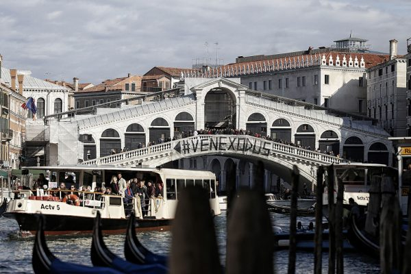 People gather on a bridge in Venice during a protest