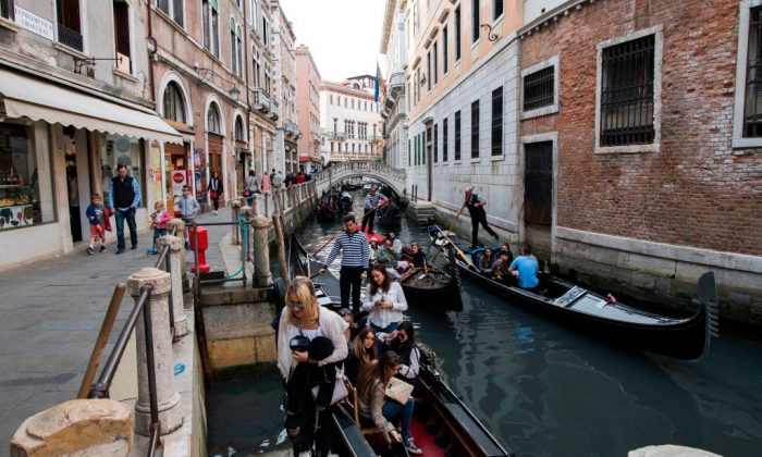 Tourists leave after a tour on a canal in Venice on April 7, 2017. (Miguel Medina/AFP/Getty Images)