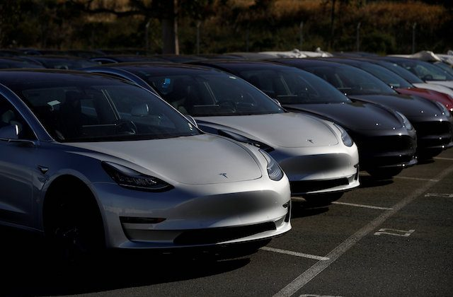 A row of new Tesla Model 3 electric vehicles is seen at a parking lot in Richmond, California, on June 22, 2018.   (Reuters/Stephen Lam)
