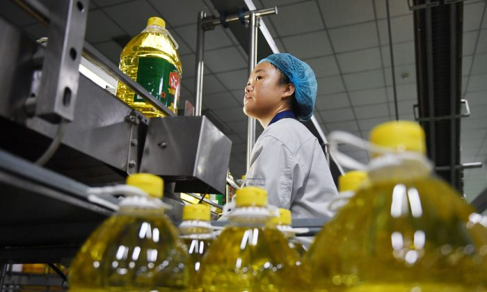 A worker monitors a soybean oil production line at an oil refinery factory in Sanhe City, Hebei Province, China, on July 19, 2018. (GREG BAKER/AFP/Getty Images)
