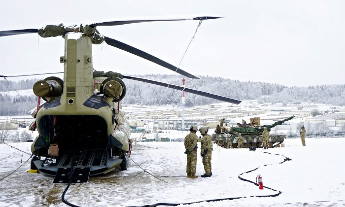 U.S. Army Soldiers work together to refuel an M1 Abrams tank during a simulated jump forward area refueling point exercise at the Hohenfels Training Area, Germany, Jan. 21, 2018. (U.S. Army photo by Sgt. Gregory T. Summers)