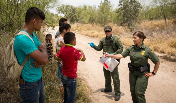 Border Patrol Agents have aliens remove their shoelaces and belongings before loading them in a van for transport in Hidalgo County, Texas