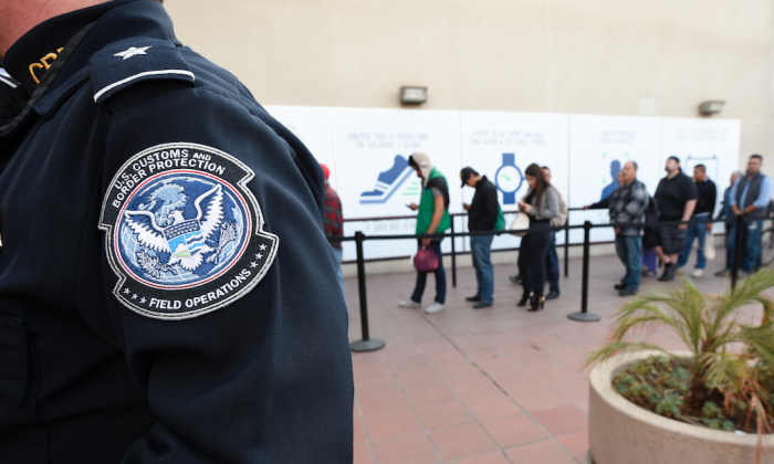 """Pedestrians crossing from Mexico into the United States at the Otay Mesa Port of Entry wait in line in San Diego. The Trump administration is proposing rules that could deny green cards to immigrants if they use Medicaid, food stamps, housing vouchers and other forms of public assistance. The Department of Homeland Security said on Sept. 22, 2018, that current and past receipt of certain public benefits above thresholds will be considered """"a heavily weighed negative factor"""" in granting green cards as well as temporary visas. (By Denis Poroy/AP)"""