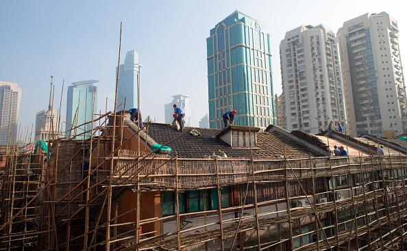 Laborers renovate the roof of a house in Shanghai on Aug. 21, 2014. (JOHANNES EISELE/AFP/Getty Images)