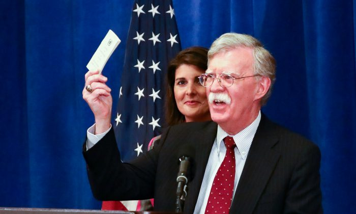 National Security Advisor John Bolton holds up a copy of the Constitution as United States Ambassador to the UN Nikki Haley looks on during a press conference before the UN General Assembly in New York City on Sept. 24, 2018. (Charlotte Cuthbertson/The Epoch Times)