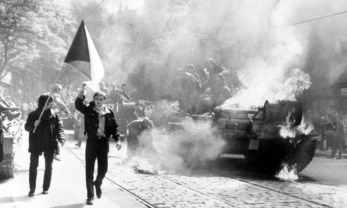 Czechoslovakians carry their national flag past a burning tank in Prague during the Soviet-led invasion of Czechoslovakia in August 1968. (Central Intelligence Agency/Public Domain)