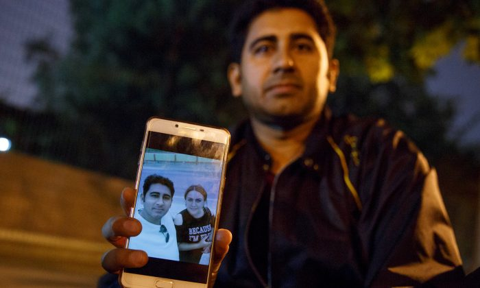 Pakistani businessman Mirza Imran Baig shows a picture of him and his wife, Mailikemu Maimati, outside the Pakistani embassy in Beijing on Sept. 25, 2018. (Thomas Peter/Reuters)