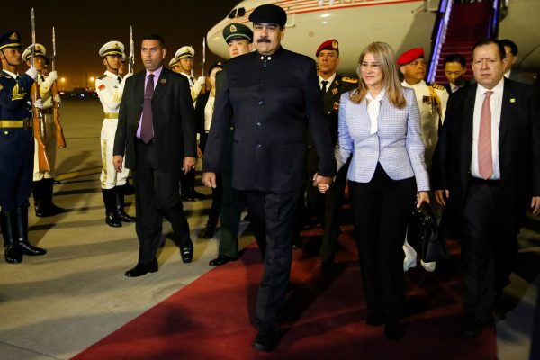 Venezuela's President Nicolas Maduro walks with his wife Cilia Flores upon their arrival at the airport in Beijing, China