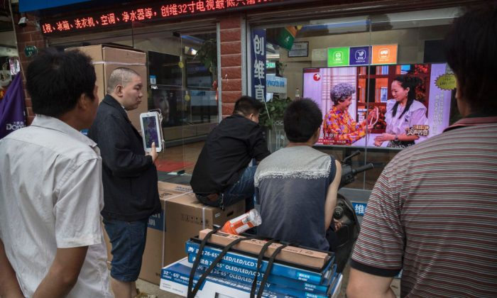 Chinese men watch a program on a large television set in the window of an electronics shop on May 15, 2017 in Wuhan, Hubei Province, China. (Kevin Frayer/Getty Images)