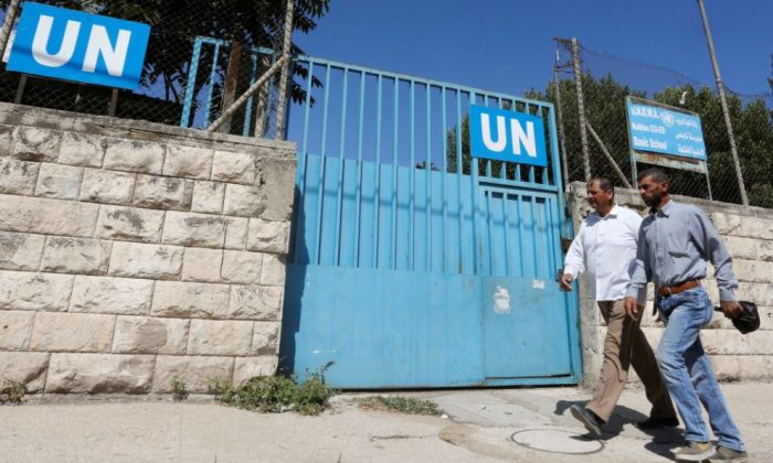 Palestinians pass by the gate of an UNRWA-run school in Nablus in the occupied West Bank Aug. 13, 2018. (Abed Omar Qusini/Reuters)