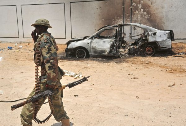 A Somali soldier patrols next to the burnt-out wreckage of a car