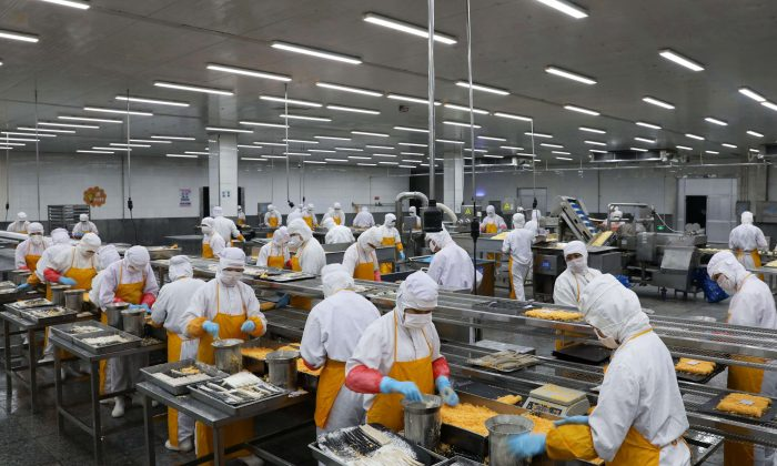 Workers process pork at a food factory in Rongcheng in Shandong Province, on July 19, 2018. (AFP/Getty Images)