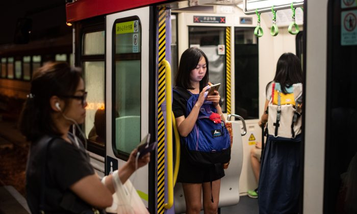 A woman looks at her mobile phone in the MTR's Light Rail as another woman waits at the platform in Tuen Mun district in Hong Kong on August 20, 2018. (PHILIP FONG/AFP/Getty Images)