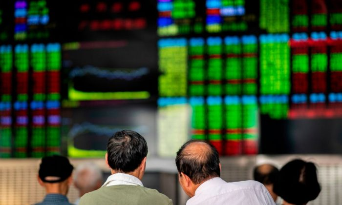 Investors monitor stock prices at a securities company in Shanghai on Sept. 25, 2018. (Johannes Eisele/AFP/Getty Images)