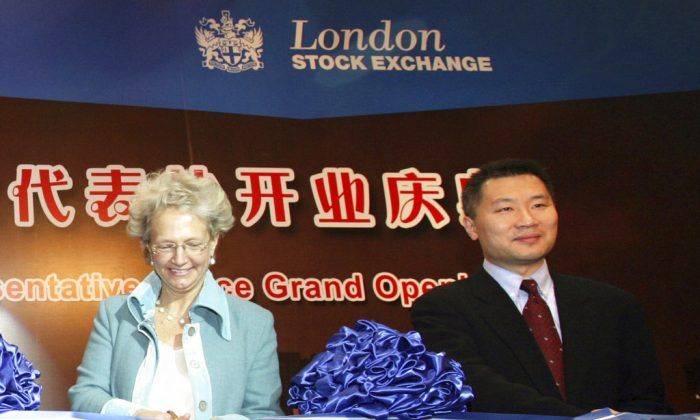 Former Chinese securities regulator Yao Gang (right) and Clara Furse, the then-Chief Executive of the London Stock Exchange, participate in a ribbon-cutting event at a business center for the LSE in Beijing on Jan. 18, 2008 (Chinatopix via AP)