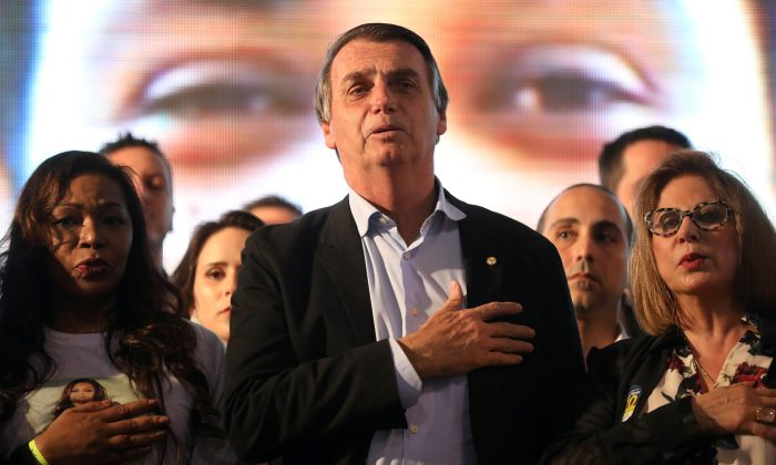 Presidential candidate Jair Bolsonaro listens to the national anthem during a meeting with women in Porto Alegre, Brazil Aug. 30, 2018.  (By Diego Vara/Reuters)