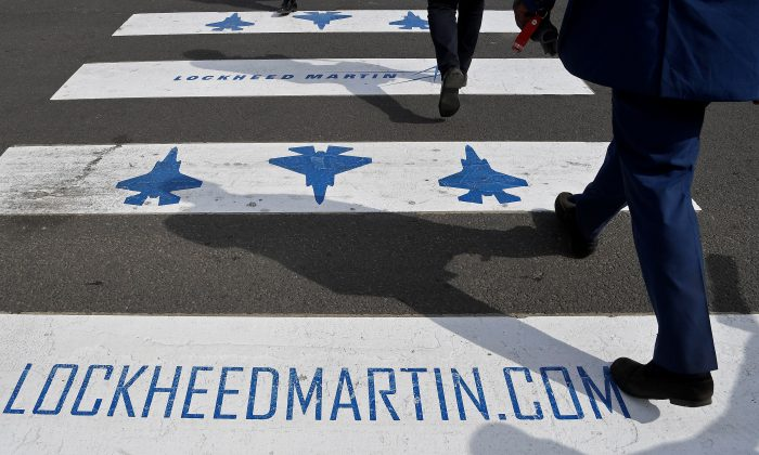 Trade visitors are seen walking over a road crossing covered with Lockheed Martin branding at Farnborough International Airshow in Farnborough, Britain, July 17, 2018. REUTERS/Toby Melville