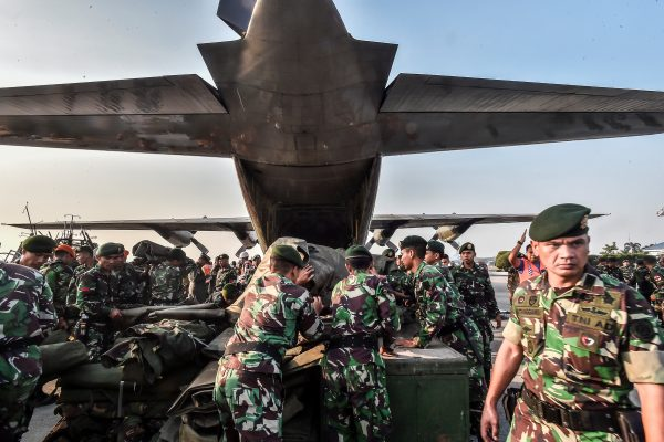 Indonesian soldiers load emergency supplies into a Hercules military plane before heading to Palu at Halim Perdanakusuma military base in Jakarta