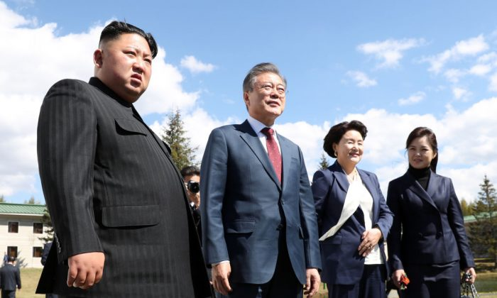 North Korea's leader Kim Jong Un (L) and his wife Ri Sol Ju (L) pose with South Korean President Moon Jae-in (2nd L) and his wife Kim Jung-sook (2nd R) during a visit to Samjiyon guesthouse in Samjiyon on Sept. 20, 2018 in Samjiyon, North Korea. (Pyeongyang Press Corps/Pool/Getty Images)