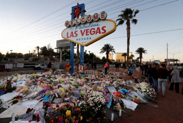 """The """"Welcome to Las Vegas"""" sign is surrounded by flowers and items, left after the October 1 mass shooting, in Las Vegas, Nevada"""