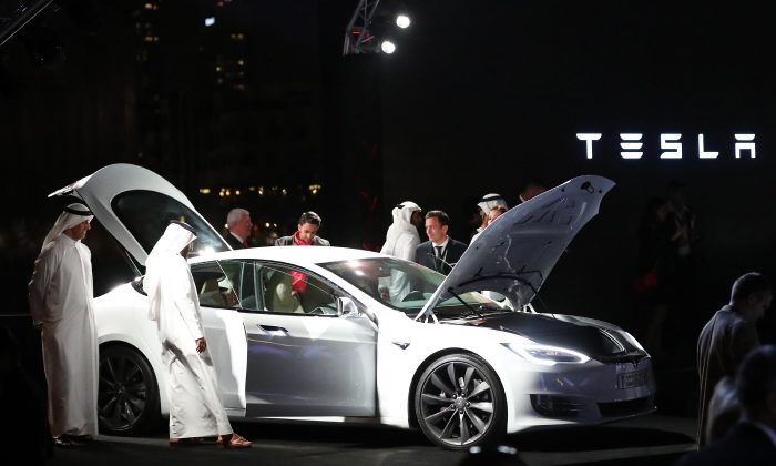 Emirates check a vehicle manufactured by Electric carmaker Tesla during a ceremony in Dubai, on Feb. 13, 2017. (Karim Sahib/AFP/Getty Images)