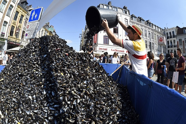 "An employee of ""La Chicoree"" restaurant empties a bucket of empty mussel shells onto a pile during the annual Braderie de Lille (Lille Fleamarket) in Lille, northern France, on Sept. 2, 2018. (FRANCOIS LO PRESTI/AFP/Getty Images)"