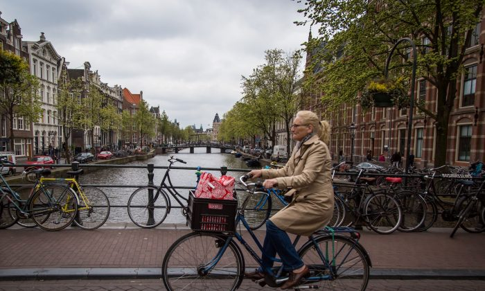 A woman rides a bicycle in Amsterdam on April 12, 2017. (Aurore Belot/AFP/Getty Images)