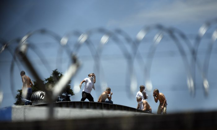 Inmates escaping from Las Gaviotas Male Juvenile Detention Centre during a riot stand on the roof of a warehouse nearby in Guatemala City, on July 3, 2017. (Johan Ordonez/AFP/Getty Images)