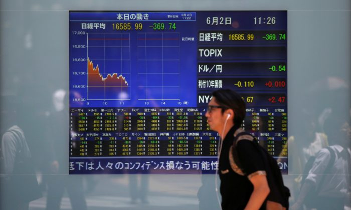 A man walks in front of a screen showing today's movements of Nikkei share average outside a brokerage in Tokyo, Japan, June 2, 2016. (Issei Kato/Reuters)