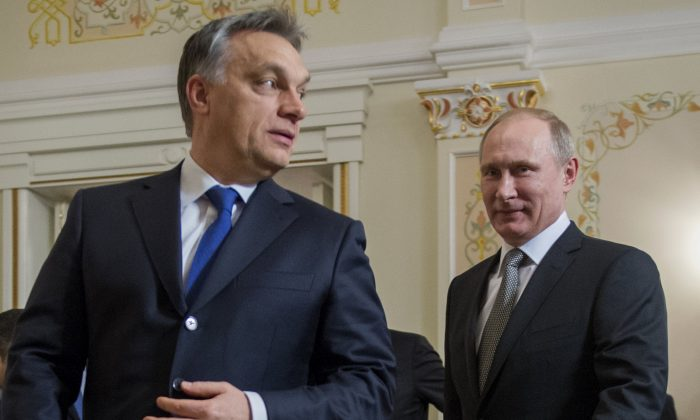 "Russian President Vladimir Putin (R) and Hungarian Prime Minister Viktor Orban walk during their meeting in the Novo-Ogaryovo residence outside Moscow on Jan. 14, 2014. Nationalist Hungarian Prime Minister Viktor Orban perceives prevailing winds as ""blowing from the East"" and sees in Russia an ideal political model for his concept of an ""illiberal state.""(AP Photo/RIA-Novosti, Sergei Guneyev, Presidential Press Service)"
