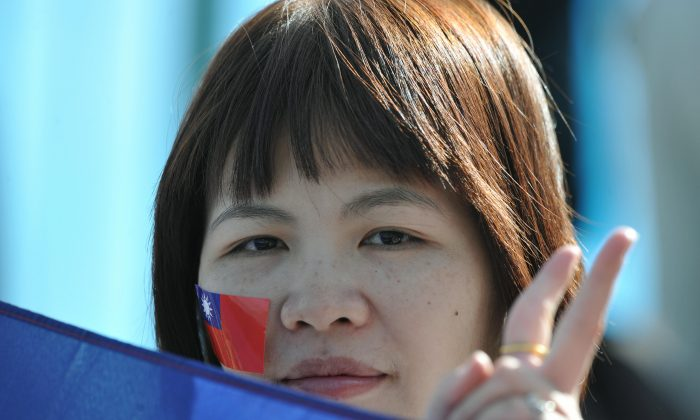 A spectator, her cheek decorated with the Taiwanese flag, gestures at the Australian Open tennis tournament on Jan. 20, 2009. (Antony Dickson/AFP/Getty Images)