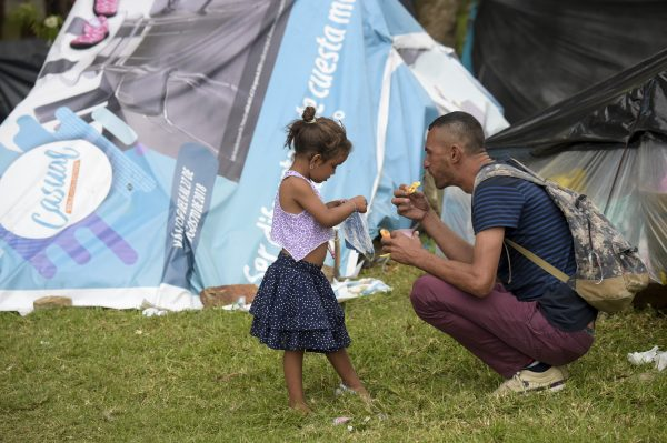 A Venezuelan migrant man and a girl at an improvised camp near the bus terminal in Bogota.