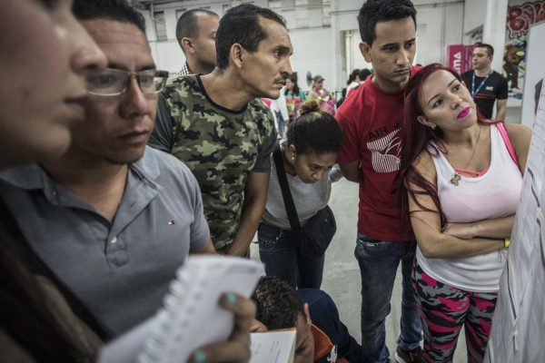 Venezuelan migrants look at job offers posted on a board during a job fair in Medellin.