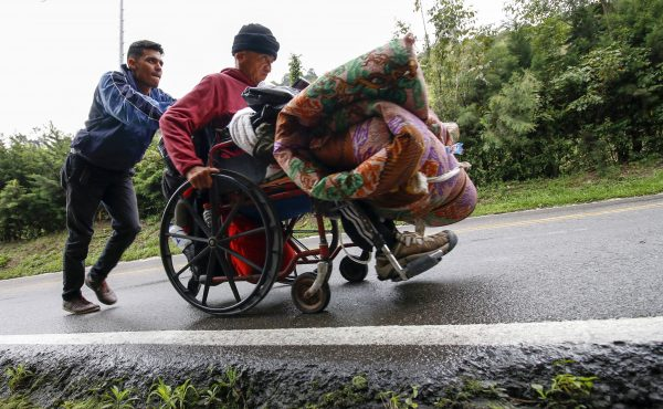 A Venezuelan migrant pushes his father's wheelchair.