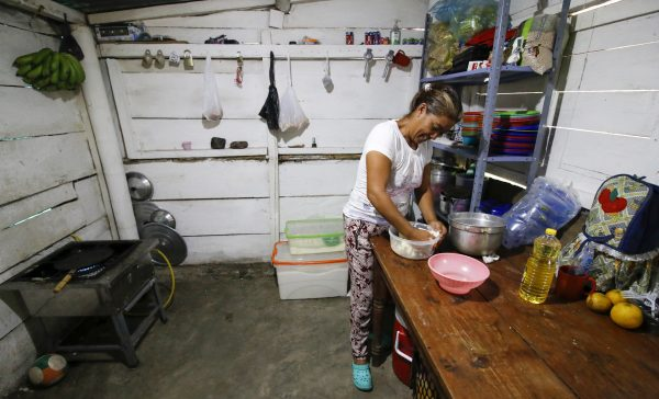 A Venezuelan migrant prepares food at an improvised shelter on the side of the road.