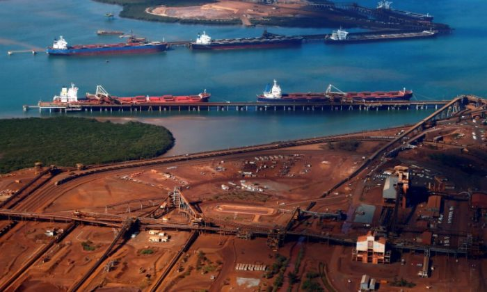 Ships waiting to be loaded are seen near piles of iron ore and bucket-wheel reclaimers at the Fortescue loading dock located at Port Hedland in the Pilbara region of Western Australia, on Dec. 3, 2013. (David Gray/Reuters)