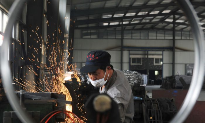 A worker welds wheel hubs of baby carriages that will be exported at a factory in Hangzhou in China's eastern Zhejiang province on June 4, 2018. - China warned the US that any deals reached during ongoing trade talks would be void if Washington went ahead with imposing tariffs on Chinese goods, as the latest round of negotiations ended on June 3 in Beijing. (-/AFP/Getty Images)