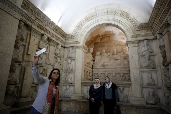A visitor uses her mobile phone to take a selfie during the reopening of Syria's National Museum of Damascus