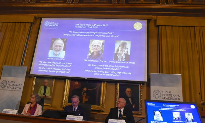 The Nobel Prize laureates for physics 2018 shown on the screen from left, Arthur Ashkin of the United States, Gerard Mourou of France and Donna Strickland of Canada during the announcement at the Royal Swedish Academy of Sciences in Stockholm, Sweden, on Oct. 2, 2018. (Hanna Franzen/TT via AP)