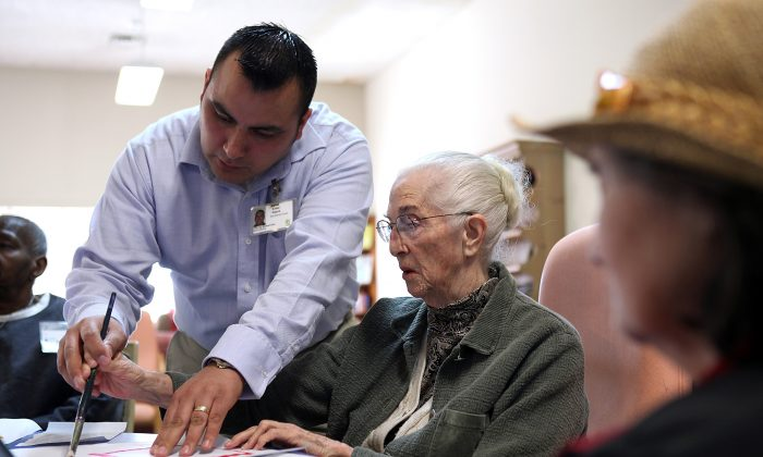 A care worker assists an elderly client during an activity session in a Day Care center in California on Feb. 10, 2011. Demand in dementia care is increasing but workforce efficiency is not keeping up. (Justin Sullivan/Getty Images)