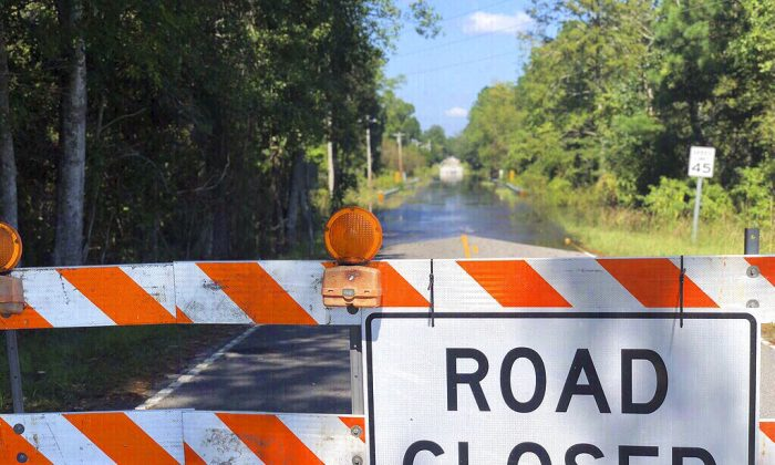 A sign stands near the Carter's Crossroads community in Georgetown County, a road adjacent to Boser Swamp is flooded over, Wednesday, Sept. 26, 2018, in Georgetown County, S.C. This is one of many lowlying areas in this and other nearby farming communities where roads are blocked off days after the rains of Florence have stopped. (Meg Kinnard/AP Photo)