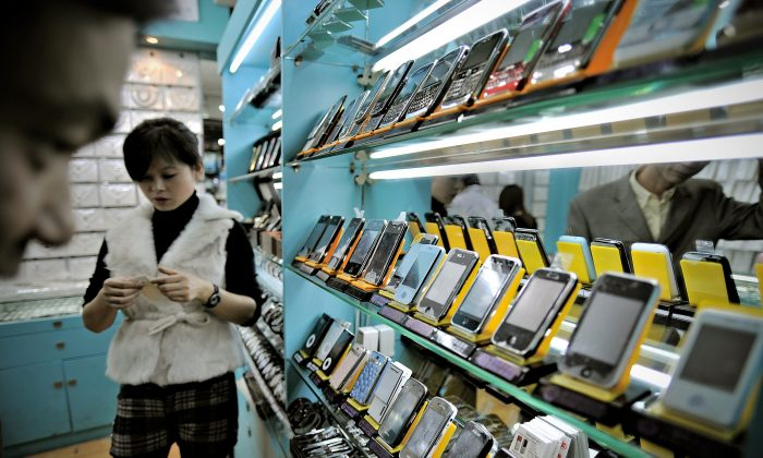 This picture taken on November 13, 2009 shows a man (L) looking at fake iPhones displayed in a shop at a market known for counterfeit US goods and housed in the metro station connected to the Science and Technology Museum in Shanghai. (PHILIPPE LOPEZ/AFP/Getty Images)