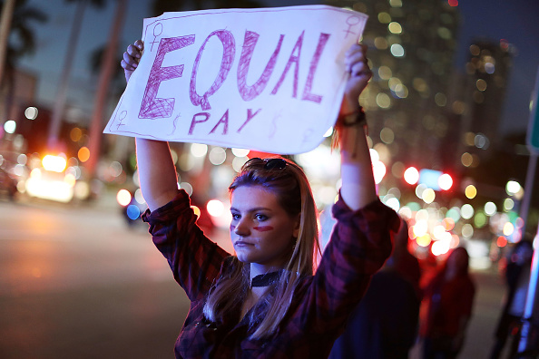 Clarissa Horsfall holds a sign reading, 'Equal Pay,' as she joins with others during 'A Day Without A Woman' demonstration on March 8, 2017 in Miami, FL. (Joe Raedle/Getty Images)