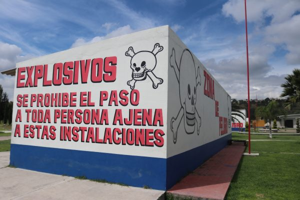 Signs warn of the dangers of fireworks at a shop in La Saucera, in Tultepec, Mexico.