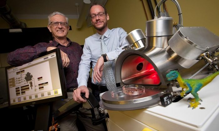 Professors Maikel Reinstadter (R) and Ralph Pudritz pose for a photo with the planet simulator in the origins of life lab at McMaster University in Hamilton, Canada on Oct. 3, 2018. (The Canadian Press/Peter Power)