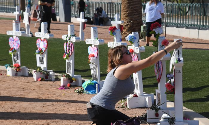 Ashley Schuck of Nevada places a medal she got for running for shooting victim Neysa Tonks in Saturday's Vegas Strong 5K on a cross set up for Tonks in Las Vegas, Nevada on Oct. 1, 2018. On Oct. 1, 2017, Stephen Paddock opened fire on the Route 91 Harvest country music festival in Las Vegas killing 58 people and injuring more than 800 in the deadliest mass shooting event in U.S. history.  (Ethan Miller/Getty Images)