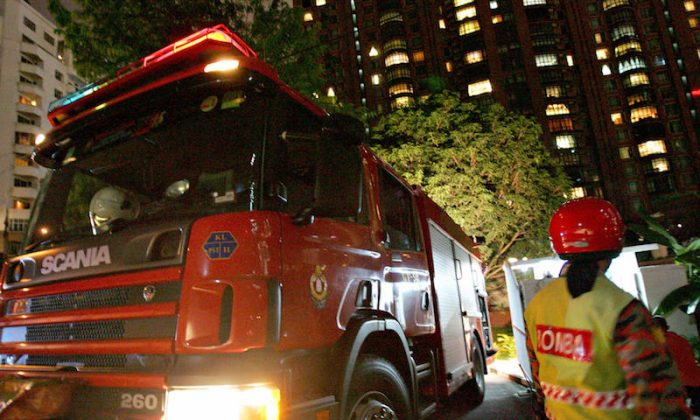 A member of the Malaysian Fire and Rescue Department (R) waits beside a fire truck at the entrance of the Philippine Embassy in downtown Kuala Lumpur in 2005. (Tengku Bahar/AFP/Getty Images)
