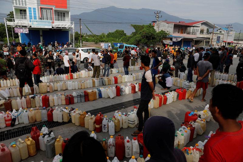 people wait to buy fuel in Palu