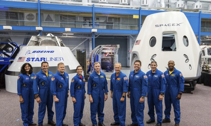 From left, Sunita Williams, Josh Cassada, Eric Boe, Nicole Mann, Christopher Ferguson, Douglas Hurley, Robert Behnken, Michael Hopkins and Victor Glover stand in front of mockups of Boeing's CST-100 Starliner and SpaceX's Crew Dragon capsules at the Johnson Space Center in Texas on Aug. 3, 2018. (NASA/AP)