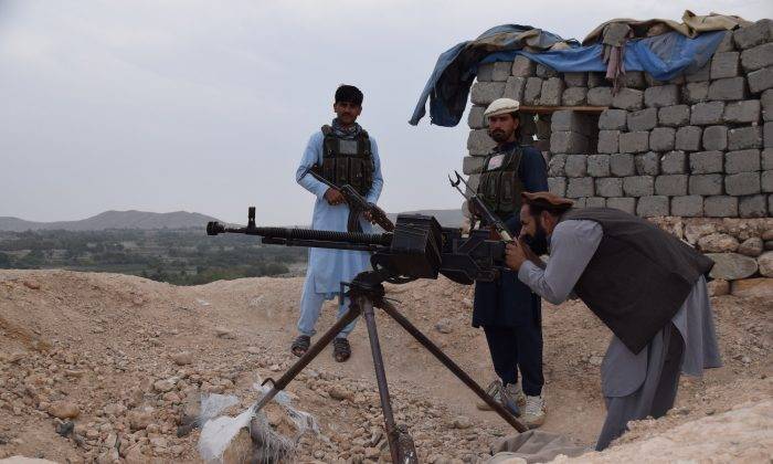 Members of an armed pro-government uprising group in an outpost just outside of Kaga, the center of the district of Khogyani in the eastern Afghan province of Nangarhar, with Malek Gul Shirin, the commander of the group, manning a heavy machine gun, on Oct. 2, 2018. (Franz J. Marty/Special to The Epoch Times)